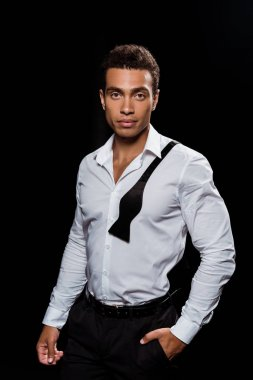handsome mixed race man looking at camera while standing with hand in pocket isolated on black