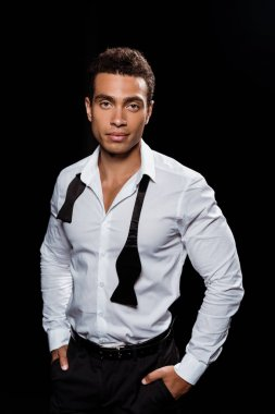 handsome mixed race man looking at camera while standing with hands in pockets isolated on black