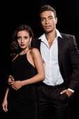 handsome mixed race man standing with hand in pocket near attractive woman isolated on black