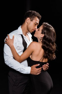 handsome mixed race man embracing and looking at elegant woman isolated on black