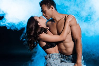 handsome mixed race man hugging beautiful and sexy girl in bra on blue with smoke