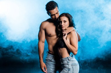 handsome mixed race man holding hands with sexy girl on blue with smoke