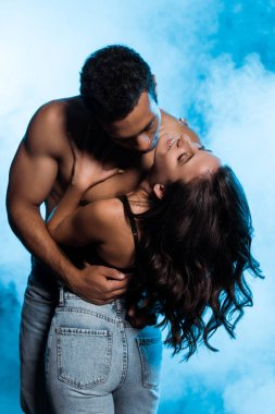 shirtless mixed race man hugging happy girl in denim jeans standing on blue with smoke