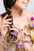 Photo cropped view of smiling woman touching braid in mesh with spring wildflowers isolated on grey