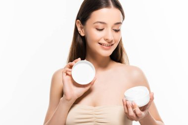 Beautiful happy young woman with perfect skin looking at cosmetic cream isolated on white stock vector