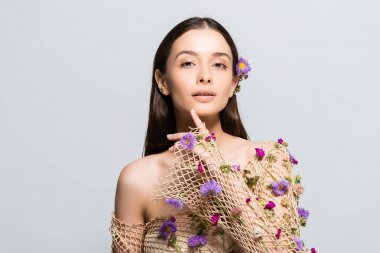 Beautiful girl in mesh beige clothing with purple flowers touching face isolated on grey stock vector