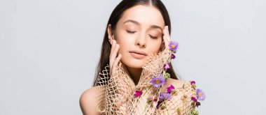 Beautiful woman with closed eyes in mesh beige clothing with purple flowers touching face isolated on grey stock vector