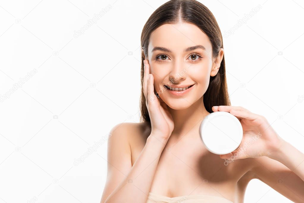Beautiful smiling young woman with perfect skin holding cosmetic cream isolated on white