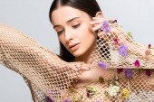 Fotografie beautiful young woman in mesh beige clothing with purple flowers posing isolated on grey