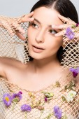 krásná žena v mřížkách béžových šatů s purpurovými květy, které se nacházejí na šedé