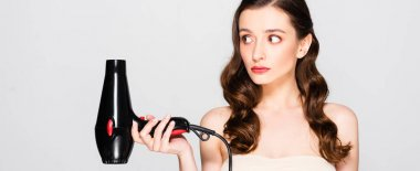 displeased beautiful brunette woman with curls and makeup holding hairdryer isolated on grey, panoramic shot