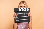 blonde woman in violet satin dress holding movie clapper board in front of face on beige background
