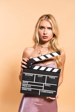 Confused blonde woman in violet satin dress with movie clapper board on beige background stock vector