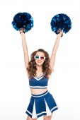 sexy happy cheerleader girl in blue uniform and 3d glasses dancing with pompoms isolated on white