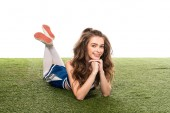 happy cheerleader girl in blue uniform lying on green field isolated on white