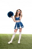 happy cheerleader girl in blue uniform and 3d glasses standing with pompom on green field isolated on white