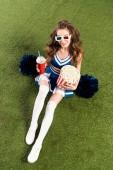 Fotografie Overhead-Ansicht von hübschen Cheerleader-Mädchen in blauer Uniform und 3D-Brille mit Pompons, Popcorn und Limo auf der grünen Wiese
