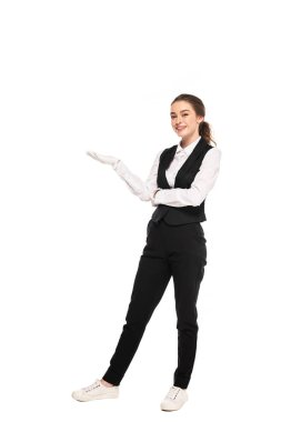 full length view of young waitress in formal wear and white gloves pointing with hand isolated on white