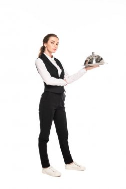 full length view of young waitress in formal wear holding dish on plate isolated on white