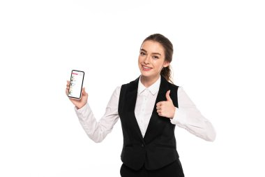 KYIV, UKRAINE - APRIL 7, 2019: happy young waitress holding smartphone with apple music app and showing thumb up isolated on white