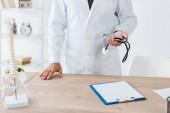 oříznutý pohled lékaře se stetoskskopem blízko schránky a stolu
