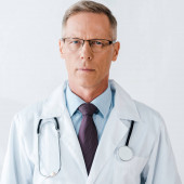 seriózní lékař v brýlích a bílém plášti, který hledí na kameru