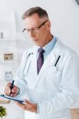 pohledný doktor v bílém plášti a při psaní brejle