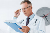 selective focus of handsome doctor in white coat looking at clipboard and touching glasses in hospital