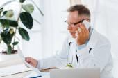 lékař v brýlích a v bílém plášti, který mluví na telefonu a dívá se na dokument