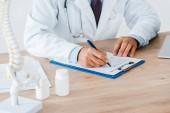 Fotografie abgeschnittene Ansicht des Arztes mit Stethoskop-Schreibdiagnose im Krankenhaus