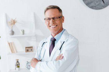 Happy doctor in white coat and glasses with crossed arms stock vector