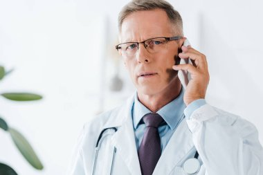 Handsome doctor looking at camera and talking on smartphone in clinic stock vector