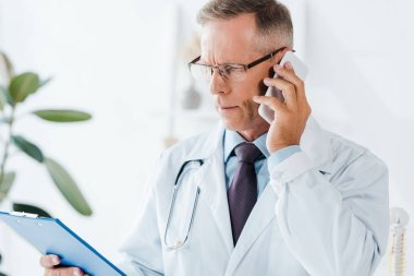 serious doctor in glasses looking at clipboard while talking on smartphone