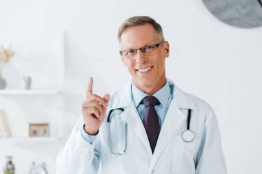 Cheerful doctor smiling while pointing with finger while looking at camera stock vector