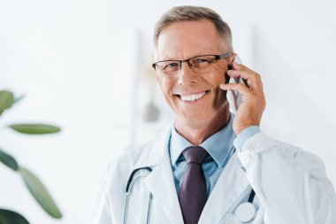 Happy doctor looking at camera and talking on smartphone in clinic stock vector