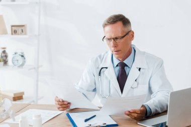 Handsome doctor in glasses looking at documents in clinic stock vector