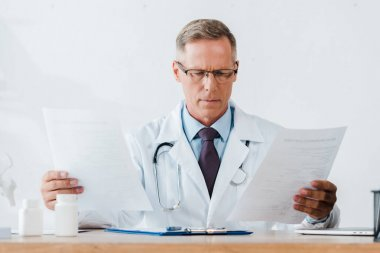 doctor in glasses and white coat with stethoscope looking at documents