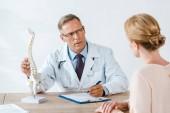 selektivní zaměření lékaře v brýlích na dotek páteře a pohled na ženu