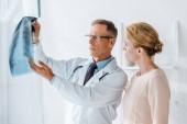 medico bello in occhiali gestendo vicino alla donna e guardando i raggi X