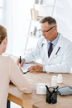 cropped view of woman near doctor in glasses writing diagnosis