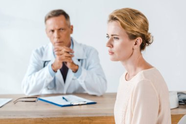 Selective focus of upset woman sitting near doctor in white coat stock vector
