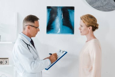 Doctor in glasses writing diagnoses on clipboard near x-ray and woman in clinic stock vector