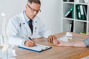 Handsome doctor measuring blood pressure of patient in clinic stock vector