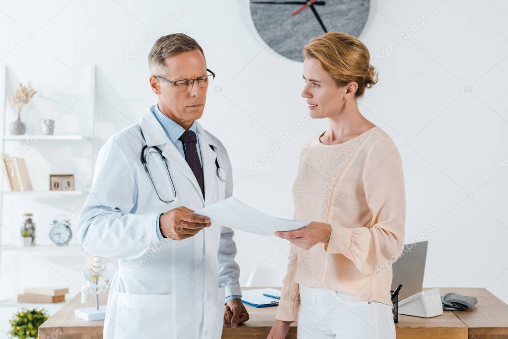 Doctor in glasses and white coat looking at document near attractive woman stock vector