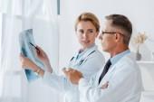 attraktiver Arzt hält Stift und Röntgen in der Nähe von Mitarbeiter gestikulieren in Klinik