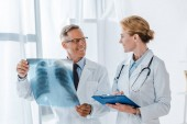 šťastný doktor držící schránku a pohled na veselého kolegu s rentgenem