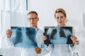 Fényképek orvos a szemüveg és vonzó munkatárs nézett röntgensugarak klinikán