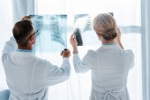 Fényképek orvos a szemüveg és munkatárs álló és néztem röntgensugarak klinikán