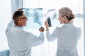 Fényképek boldog doktor a szemüveg és gyönyörű munkatárs gazdaság röntgensugarak a klinikán