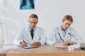 bel medico e collega attraente scrivere diagnosi in clinica